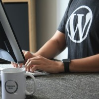 person typing on a computer wearing a shirt with the logo for wordpress